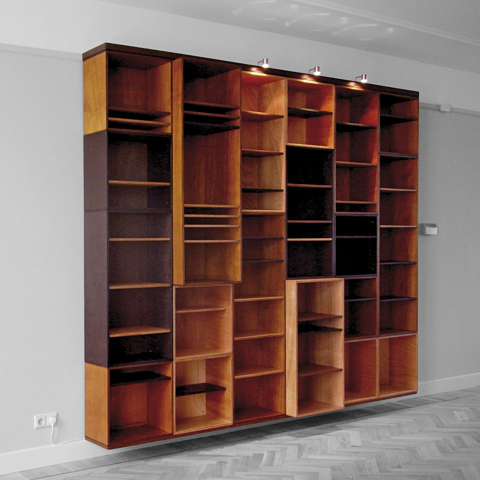 Modular Bookcase #2 - G&J by Erik Cox - Floating bookcase with 50 shelves, built up of modules based on (multiples of) 47cm, that echos the horizontal lines of the room. | In three colours (black, brown and natural wood). - Outer dimensions: 235 x 282 cm. - With the exception of two units 40 cm deep, the whole bookcase has a depth of 30 cm.